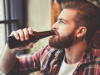 Bearded hipster drinking from a beer bottle