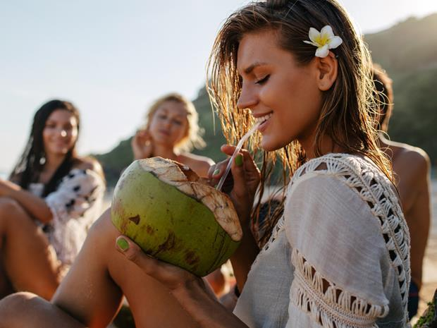 Young woman drinking coconut water from a coconut