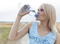 Blonde woman drinking bottled water