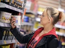 Shopper looks at labelling on tin on shelf