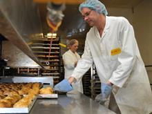 WC Rowe makes living wage commitment, man in bakery baking bread