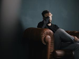 man sitting on a sofa with head in hand mental health depression sad