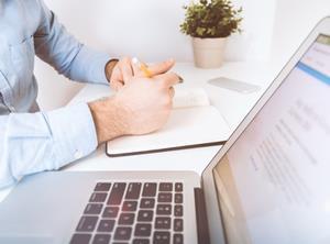 man at laptop writing