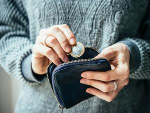 Woman putting coins into a purse_living wage_money